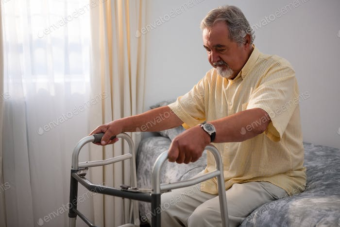 Man holding walker while sitting on bed in nursing home