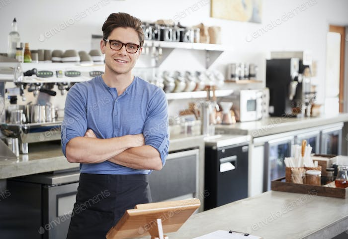 Male coffee shop owner behind the counter, arms crossed