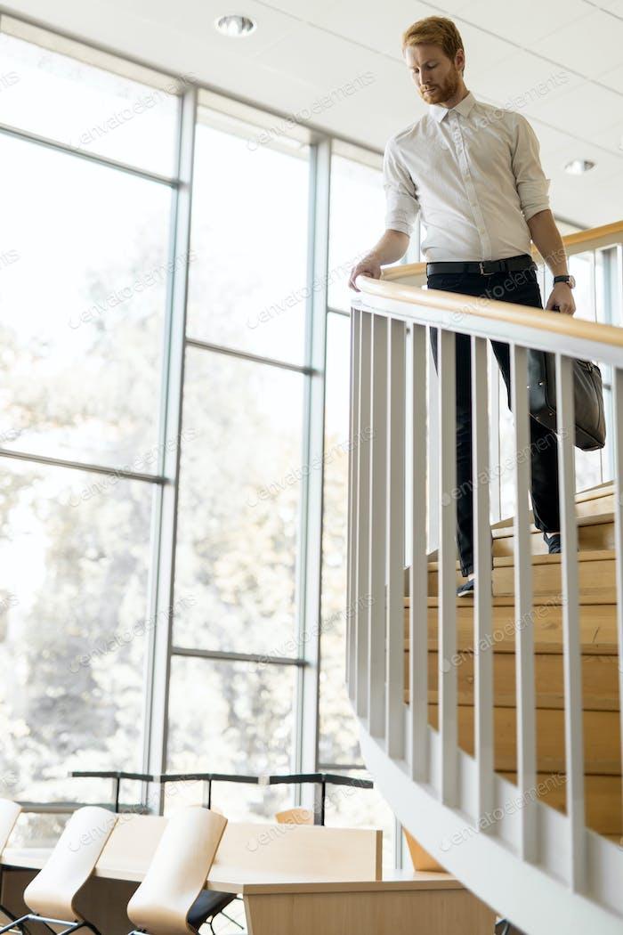 Geschäftsmann geht die Treppe hinunter, während er eine Tasche hält