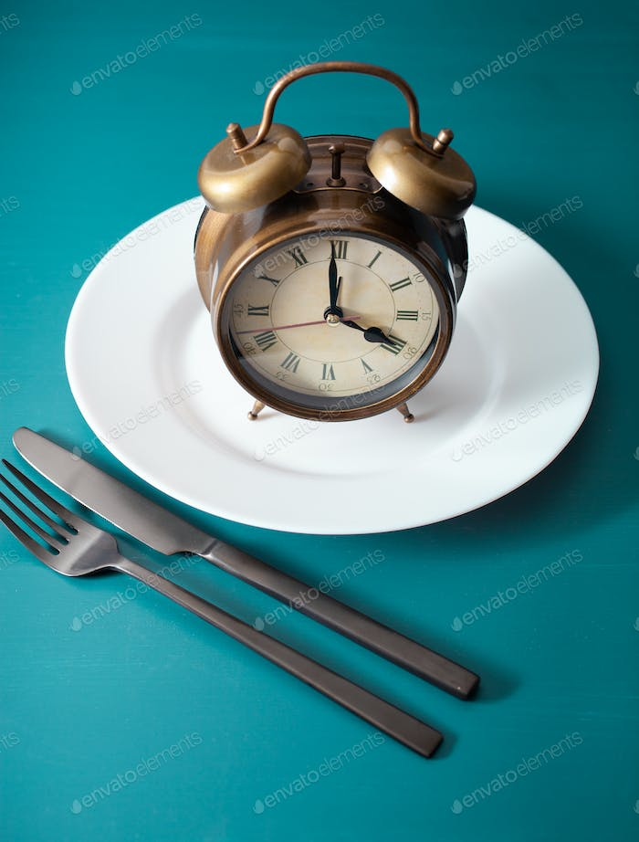 concept of intermittent fasting, ketogenic diet, weight loss. fork and knife on plate alarmclock