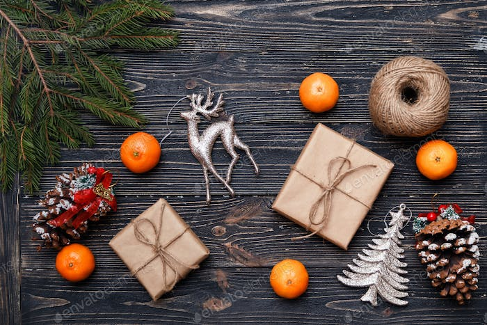 Christmas gifts packed in kraft paper on wooden background.