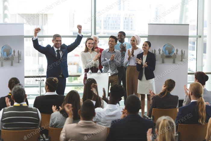 Businessman standing with arms up to victory at podium with colleagues at business seminar in office