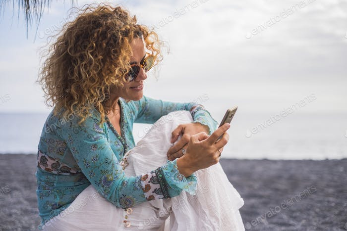 Nice cheerful caucasian woman with boho trendy clothes use modern technology cellular phone