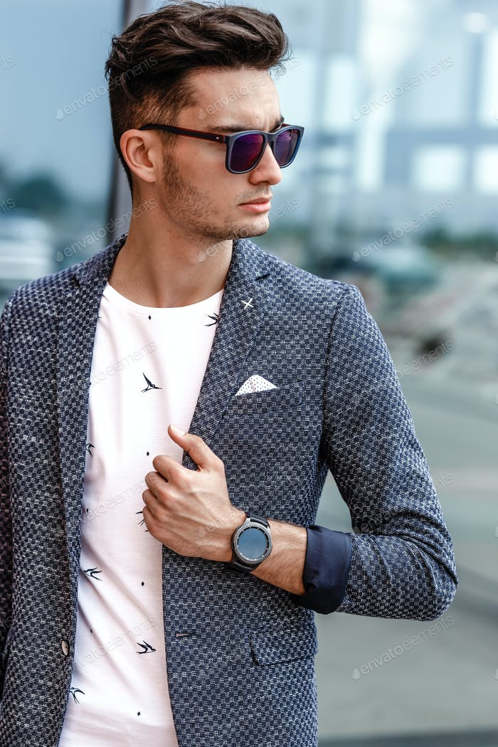 Stylish guy dressed in trendy summer clothes in casual style and sunglasses posing against the