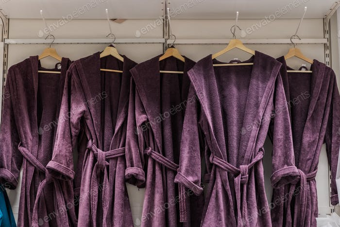 Bathrobe hanger in wardrobe. Four purple color bathrobes on a hangers