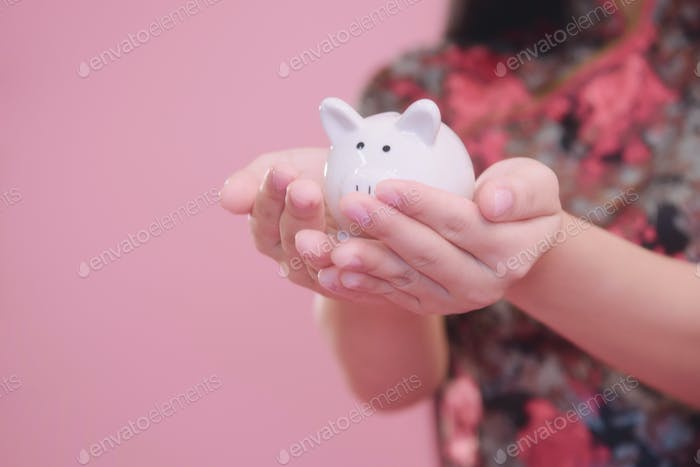 Kleines Sparschwein in der Hand.
