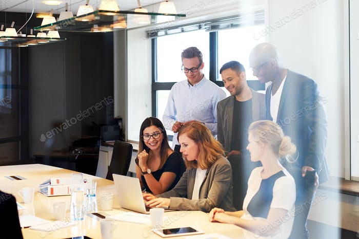 Group of executives gathered around laptop