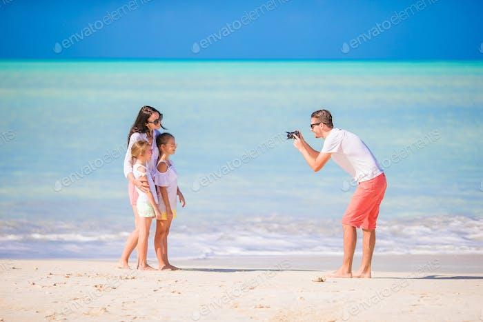 Mann, der ein Foto von seiner Familie am Strand macht