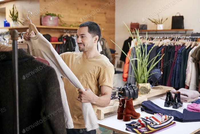 Young Hispanic man looking at clothes in a clothes shop