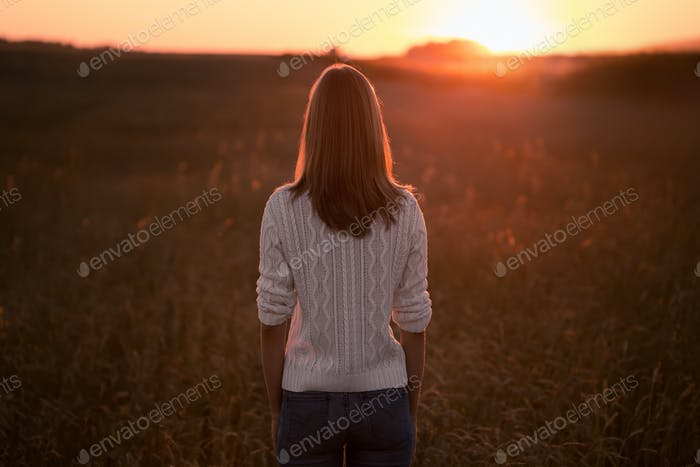 Young Woman Standing On A Wheat Field And Looking At Sunrise.