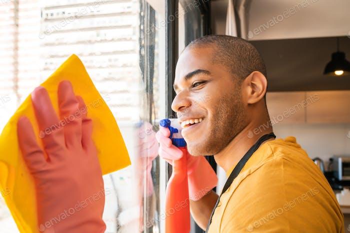 Мужчина домработница чистит стеклянное окно дома.