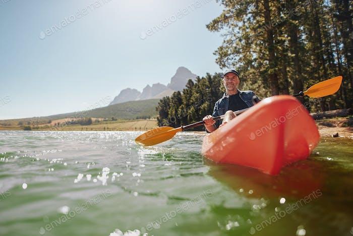 Senior Mann Kanu in einem See an einem sonnigen Tag