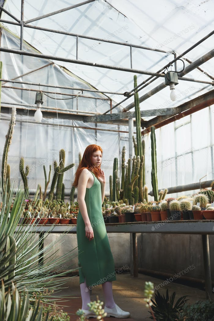 Girl standing in a glass house full of cacti