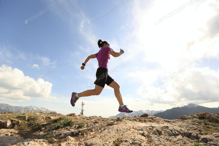 Successful woman trail running on mountain top