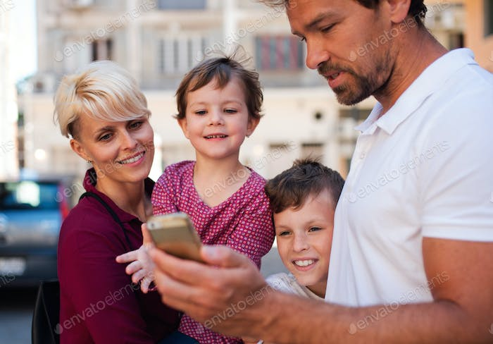 Young family with two small children standing outdoors in town, using smartphone