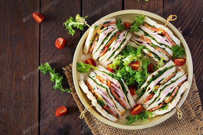 Club-Sandwich mit Schinken, Tomaten, Gurken, Käse und Rucola auf hölzernem Hintergrund. Ansicht von oben