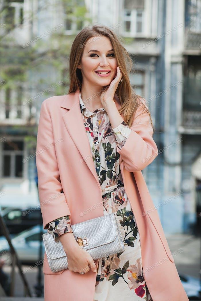 retrato de atractiva mujer sonriente elegante caminando calle de la ciudad en abrigo rosa