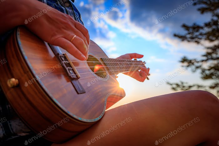 Woman at sunset holding a ukulele