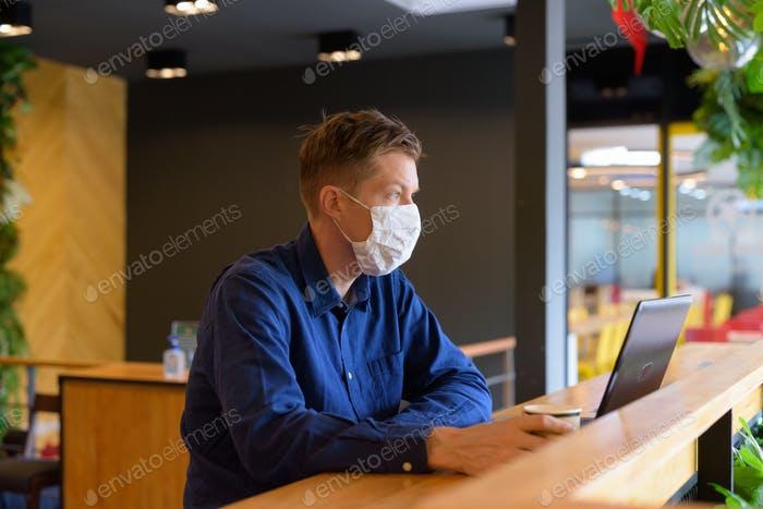 Young businessman with mask thinking and sitting with distance inside the coffee shop