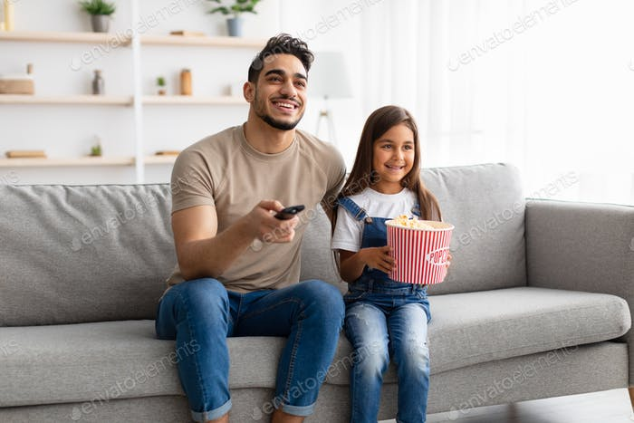 Happy family watching television sitting on couch