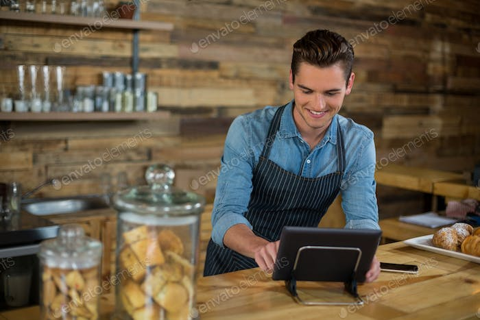 Smiling waiter standing at counter using digital tablet
