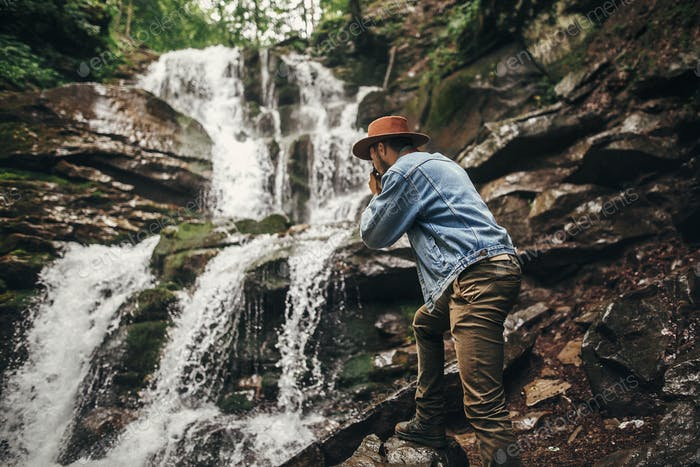 Hipster man in hat with photo camera, taking images of waterfall in forest in mountains