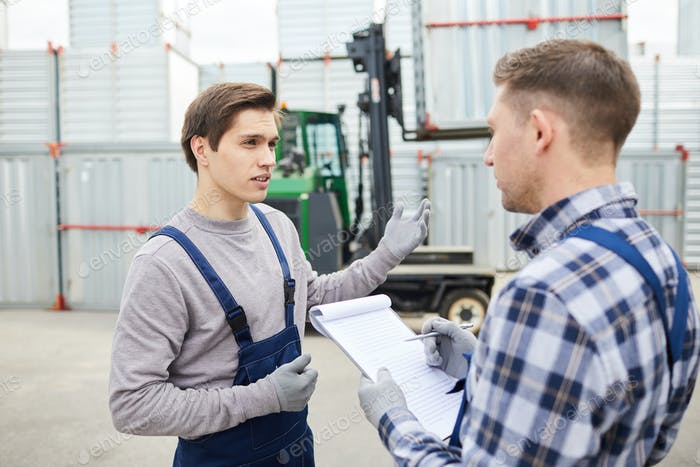 Young cargo employee asking foreman about loading