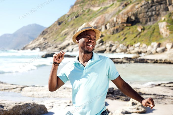 Young african man dancing at the beach