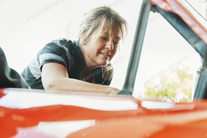 Mature woman repairing a car, looking under bonnet.