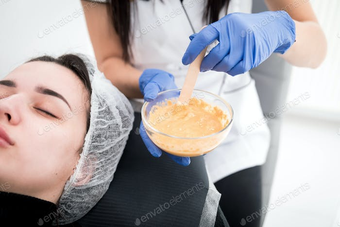 Beautician applying facial mask at cosmetic clinic, cosmetology treatment skincare face