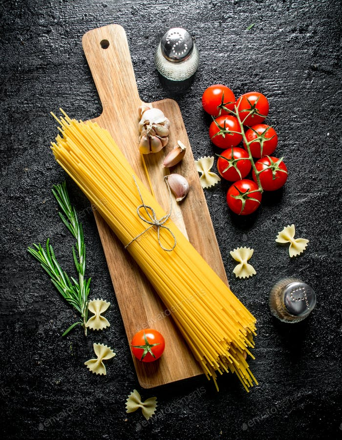 Raw spaghetti on a wooden cutting Board with garlic, tomatoes and rosemary.
