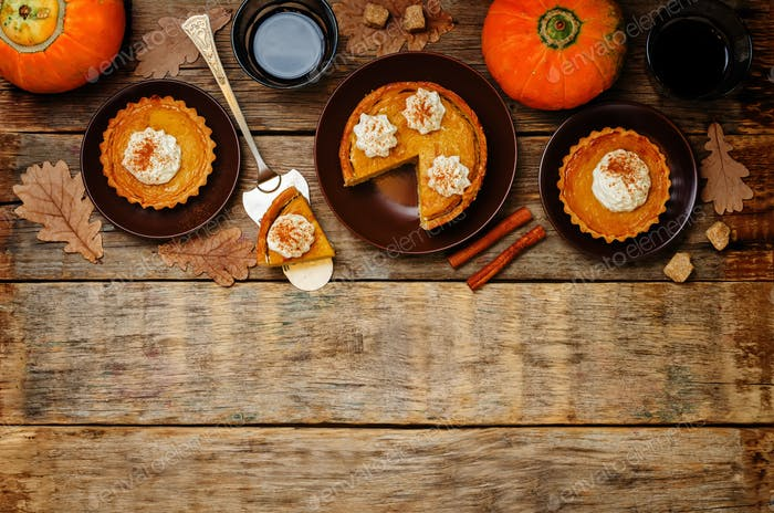 wooden background with pumpkin pies, pumpkin and coffee. Autumn