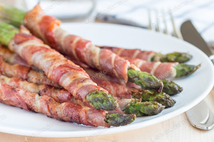 Green asparagus wrapped with bacon on white plate, horizontal