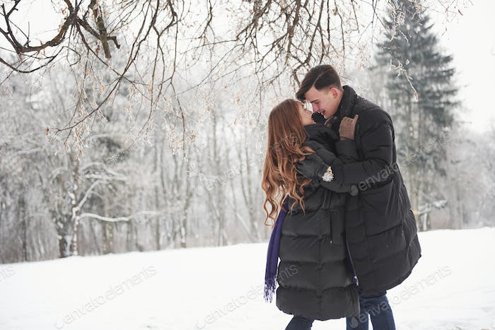 After second will be a kiss. Gorgeous young couple have good time together in snowy forest