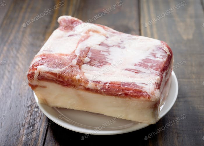 block of iberian bacon on wooden board