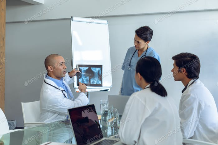 Diverse medical team discussing over x-ray report at the table of conference room