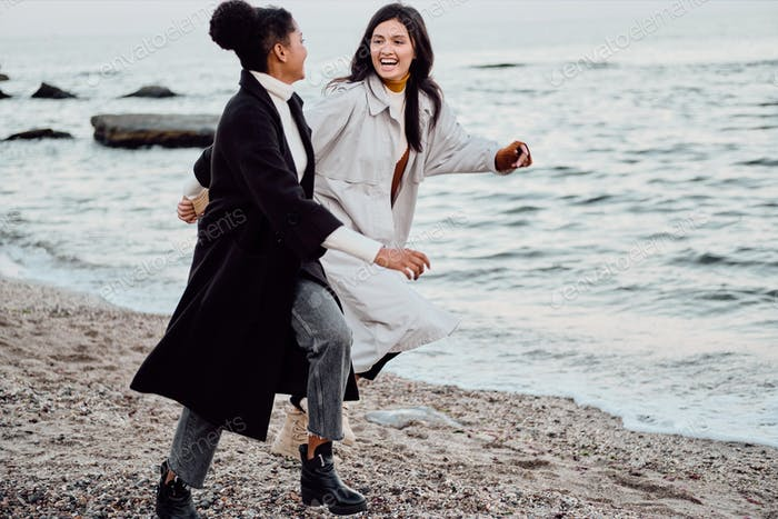 Two beautiful stylish girls in trench coats happily running by the sea