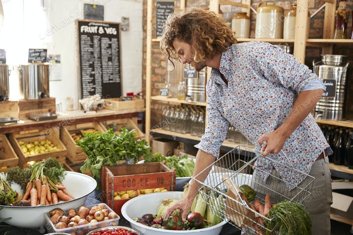 Man Buying Fresh Fruit And Vegetables In Sustainable Plastic Free Grocery Store