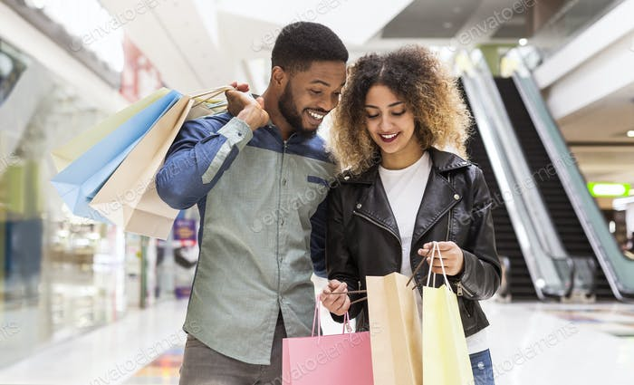 Happy african american couple discussing purchases and smiling