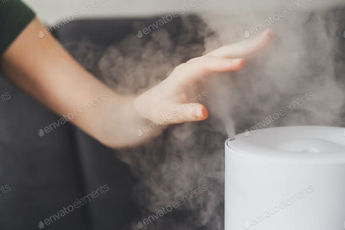 Healthy air. The humidifier distributes steam in the living room. Woman keeps hand over vapor
