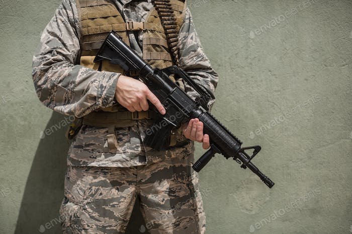 Mid section of military soldier standing with a rifle against concrete wall