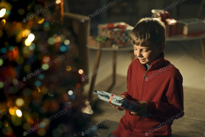 Happy boy holding a Christmas gift