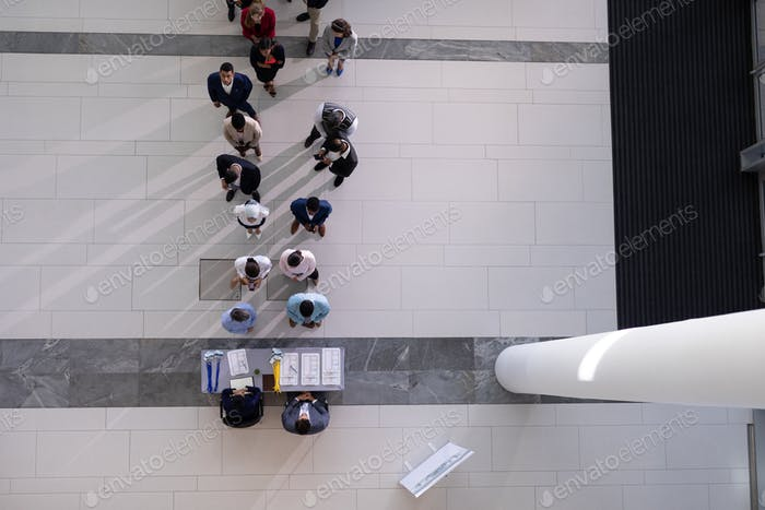 High angle view of multi-ethic group business people standing in queue at office