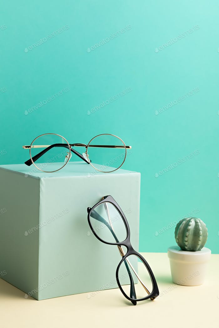 Stylish eyeglasses over pastel  background. Optical store, glasses selection, eye test idea