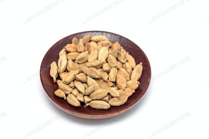 Heap of spice cardamom on a wooden plate, isolated on white back