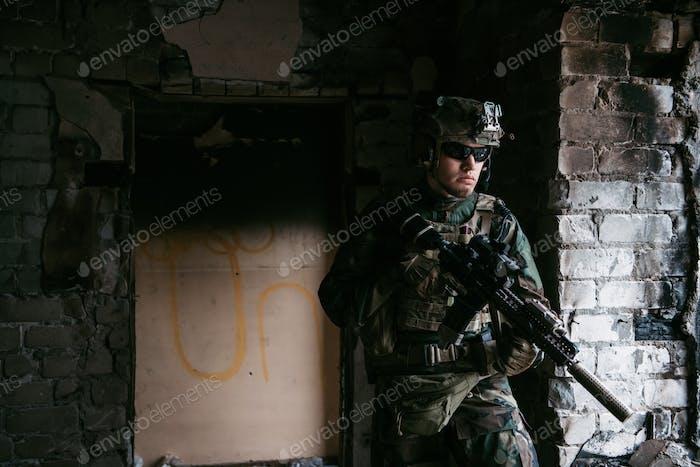 Soldat im Kampf. Urbane Kampftraining, Soldat betritt verlassenes Gebäude. Antiterrorismus