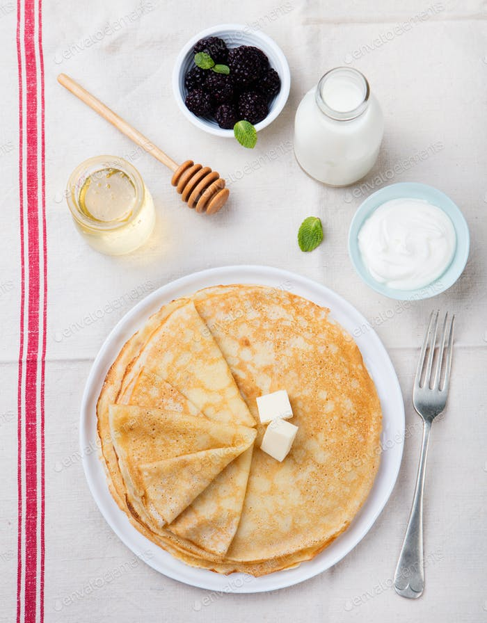 Thin crepes or pancakes with butter, honey and sour cream on a rustic textile background Top view