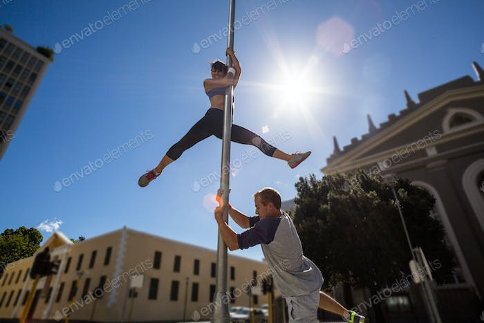 Extreme athletes hanging on street sign in the city