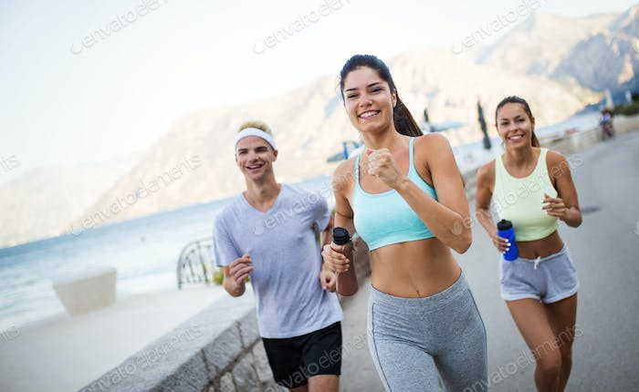 Happy fit people running and jogging together in summer sunny nature