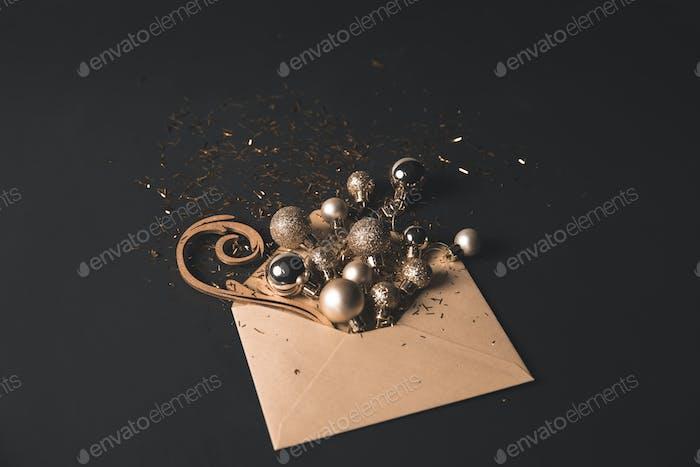 golden christmas balls in kraft envelope on black
